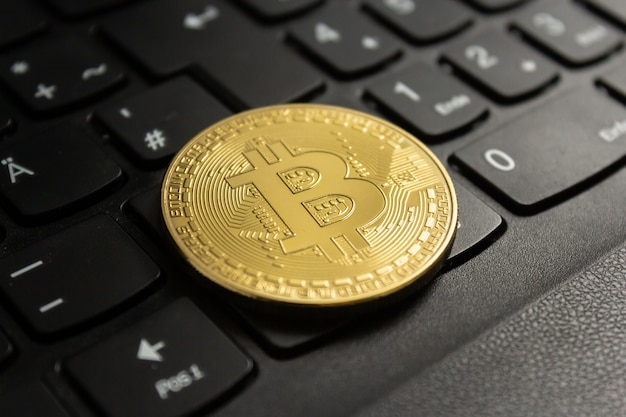 Close-up shot van een bitcoin op een zwart computertoetsenbord Gratis Foto