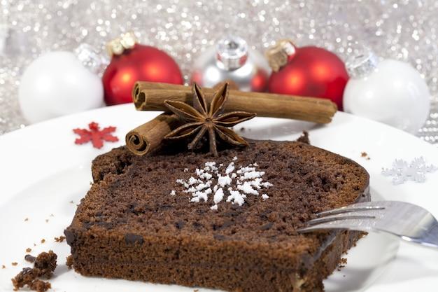 Close-up shot van een brownie met kaneel en rode kerstboom kerstballen op de achtergrond Gratis Foto