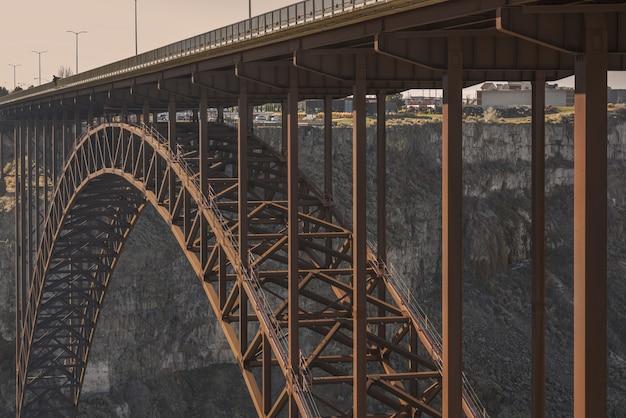 Close-up shot van een brug in het midden van kliffen met stadsgebouwen in de verte overdag Gratis Foto