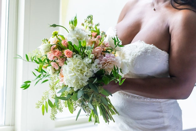 Close-up shot van een bruid in een witte jurk met een bloemboeket Gratis Foto