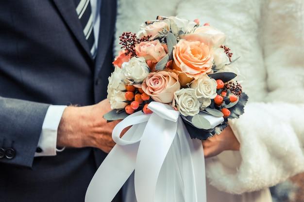Close-up shot van een bruidspaar met een bloemboeket met witte en oranje rozen Gratis Foto