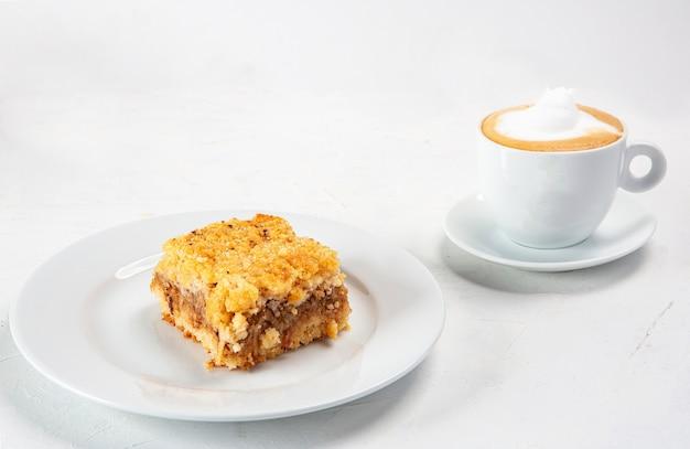 Close-up shot van een dessertbord in de buurt van een kopje cappuccino geïsoleerd op een witte achtergrond Gratis Foto