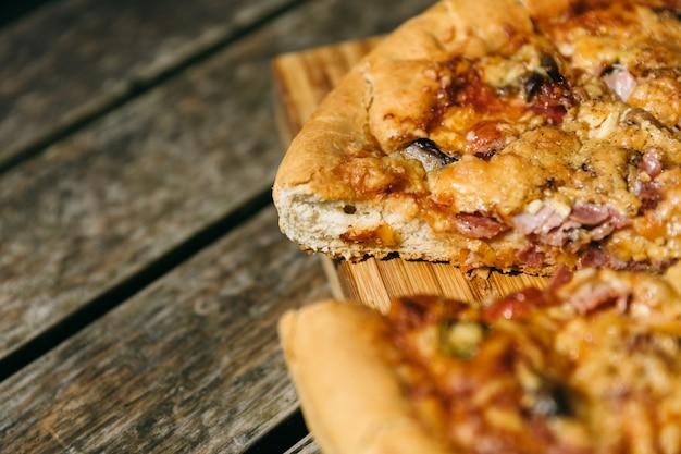 Close-up shot van een gesneden pizza op een houten bureau Gratis Foto