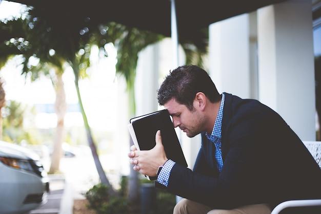 Close-up shot van een goed geklede mannelijke vergadering terwijl de bijbel tegen zijn hoofd Gratis Foto