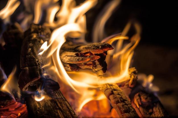 Close-up shot van een kampvuur met brandend hout en een open vlam 's nachts Gratis Foto
