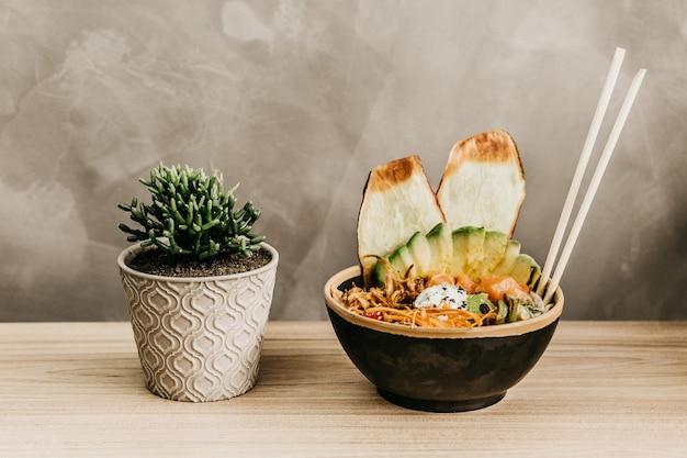 Close-up shot van een kom vol met voedsel en een plant pot op een houten tafel Gratis Foto