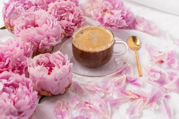 Close-up shot van een kopje oploskoffie op een schoteltje op tafel met roze pioenrozen erop Gratis Foto