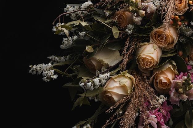 Close-up shot van een luxe boeket oranje rozen en witte bloemen op een zwarte Gratis Foto