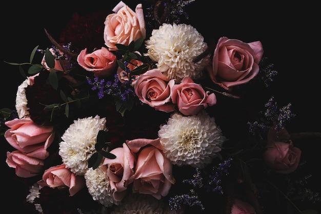 Close-up shot van een luxe boeket roze rozen en witte, rode dahlia's op een zwarte Gratis Foto