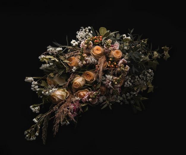 Close-up shot van een luxe boeket van oranje en bruine rozen op een zwarte achtergrond Gratis Foto