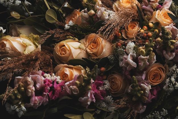 Close-up shot van een luxe boeket van oranje en bruine rozen op een zwarte Gratis Foto