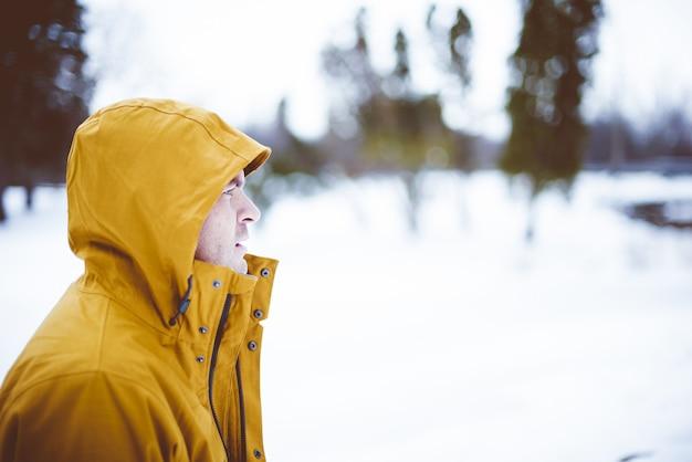 Close-up shot van een man met een gele winterjas Gratis Foto