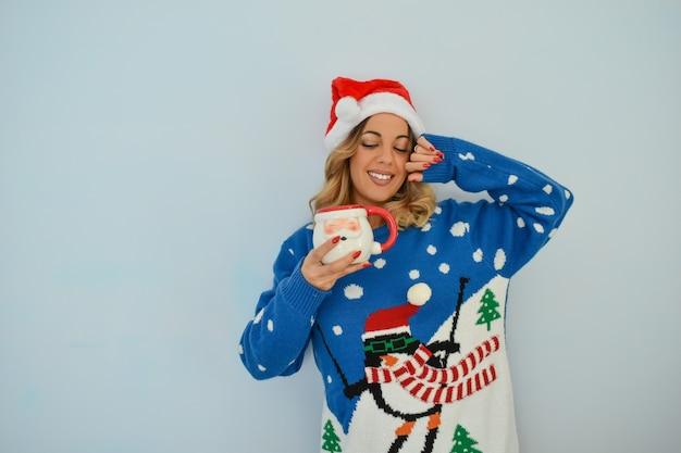 Close-up shot van een mooie jonge dame, gekleed in een kerst jurk en hoed met een kerstman beker Gratis Foto