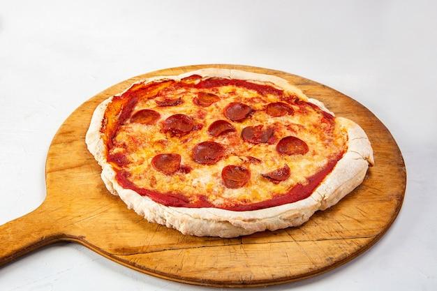 Close-up shot van een pepperoni pizza geïsoleerd op een witte achtergrond Gratis Foto