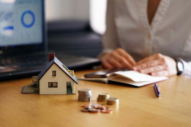 Close-up shot van een persoon die denkt aan het kopen of verkopen van een huis Gratis Foto
