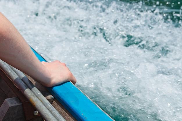 Close-up shot van een persoon die zijn hand op het schip op zee legt Gratis Foto
