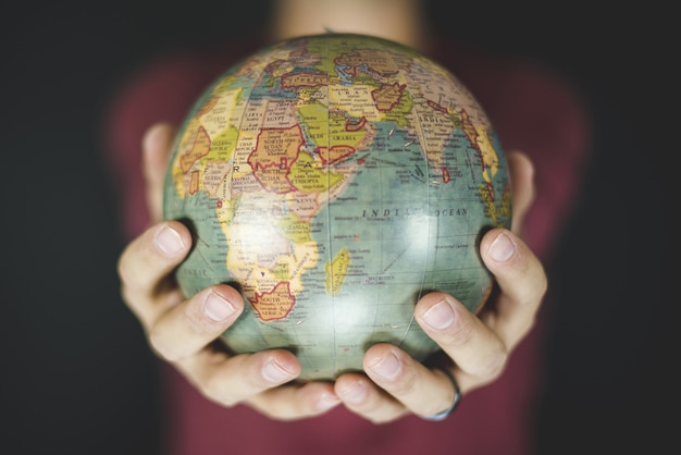 Close-up shot van een persoon met een kleine wereldbol met twee handen Gratis Foto