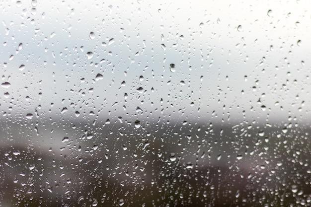 Close-up shot van een raam op een regenachtige dag, regendruppels die door het raam rollen Gratis Foto