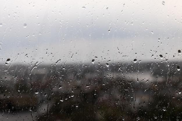 Close-up shot van een raam op een regenachtige sombere dag, regendruppels rollen door het raam Gratis Foto