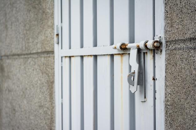 Close-up shot van een roestig slot op een metalen grijze deur Gratis Foto