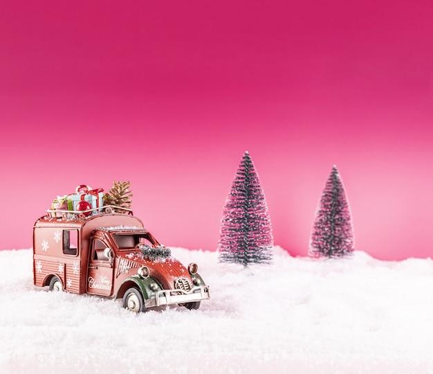 Close-up shot van een speelgoedauto voor kerstversiering op sneeuw Gratis Foto