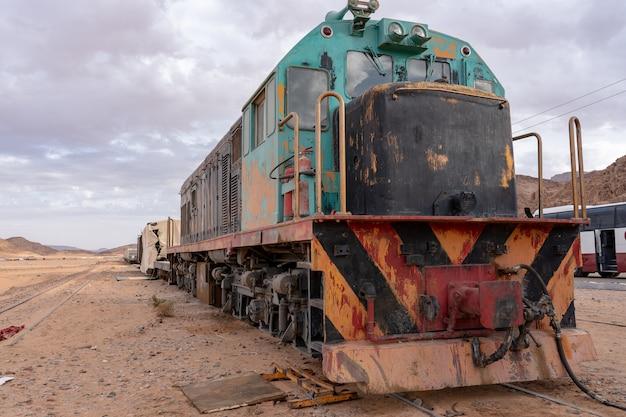 Close-up shot van een trein op een woestijn onder een bewolkte hemel Gratis Foto