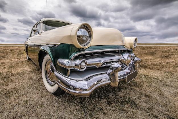 Close-up shot van een voertuig op een droog veld onder een bewolkte hemel Gratis Foto