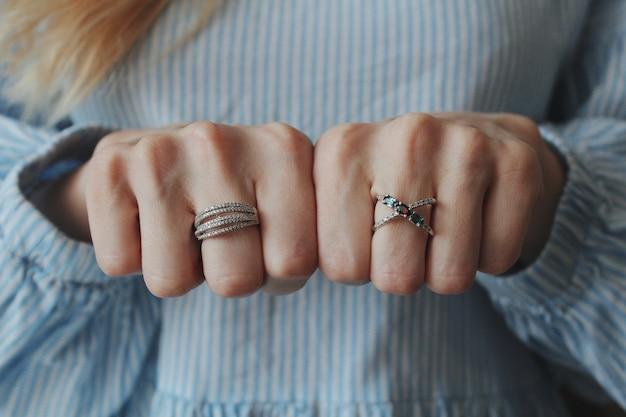 Close-up shot van een vrouw die mooie ringen aan beide handen draagt en met vuisten toont Gratis Foto