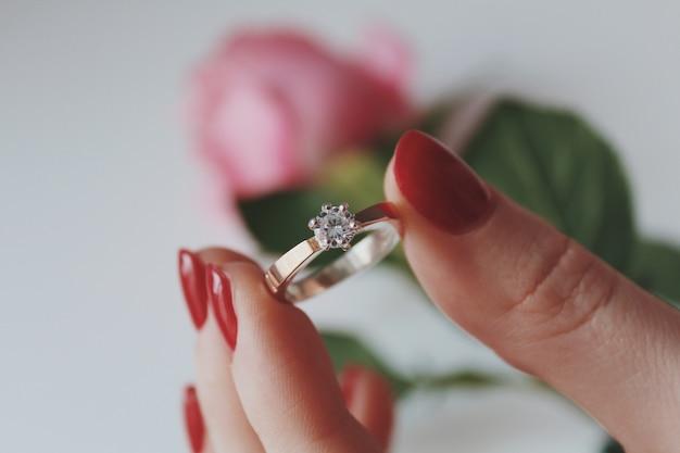 Close-up shot van een vrouw met een gouden diamanten ring met een roze roos Gratis Foto
