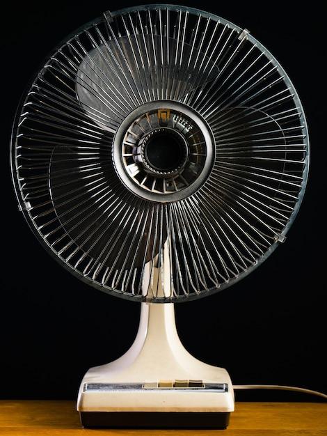 Close-up shot van een witte bureau-ventilator op een houten tafel Gratis Foto