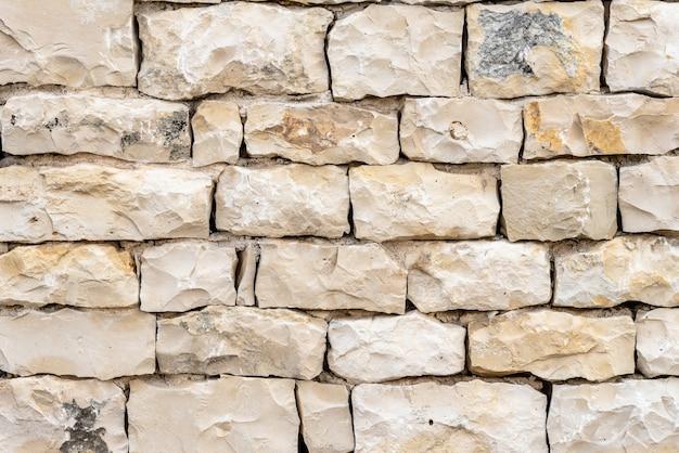 Close-up shot van een witte stenen muur, een goede achtergrond Gratis Foto