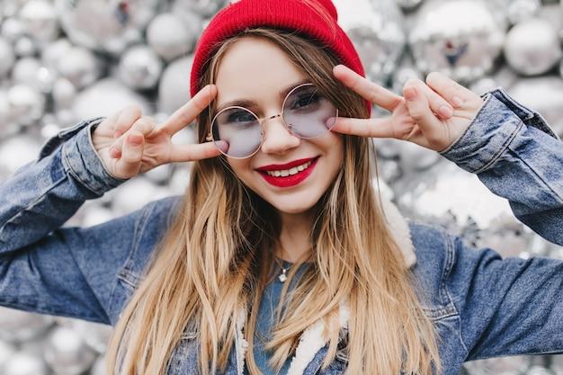 Close-up shot van enthousiaste blonde meisje poseren met vredesteken voor discoballen. portret van blije europese vrouw die in denimjasje geluk uitdrukt. Gratis Foto