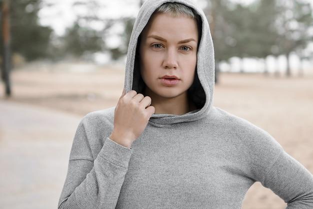 Close-up shot van fit zelfverzekerde jonge vrouw die actieve gezonde levensstijl kiest, buitenshuis traint om een perfecte lichaamsvorm te krijgen en af te vallen, poseren geïsoleerd in stijlvolle hoodie, camera kijken Gratis Foto