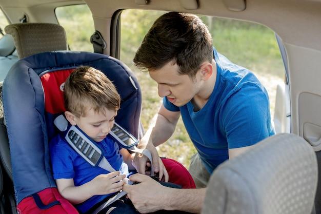 Close-up shot van geconcentreerde vader die zijn zoon helpt om de riem op de autostoel vast te maken. veilig vervoer van kinderen. Premium Foto