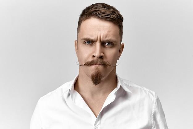 Close-up shot van gefrustreerde jonge man met stijlvol kapsel, snor en stoppels, fronsende wenkbrauwen en tuitende lippen, met een ongemakkelijke perplexe uitdrukking, bezorgd over problemen op het werk Gratis Foto
