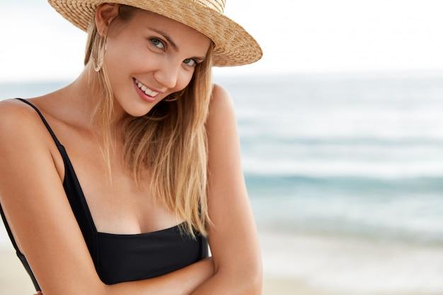 Close-up shot van gelukkig jong vrouwelijk model draagt zwarte bikini en zomerhoed, heeft positieve uitdrukking, tevreden met buitenwandeling over de kustlijn van de oceaan, heeft rust en een goed resort in de tropen. Gratis Foto