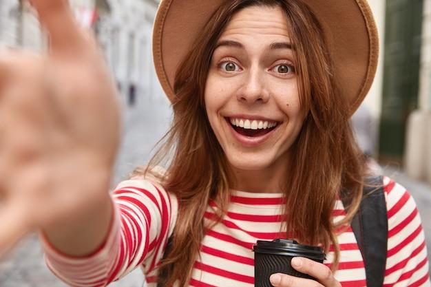 Close-up shot van gelukkig vrouwelijke reiziger heeft uitgestrekte handen naar de camera, maakt selfie portret Gratis Foto