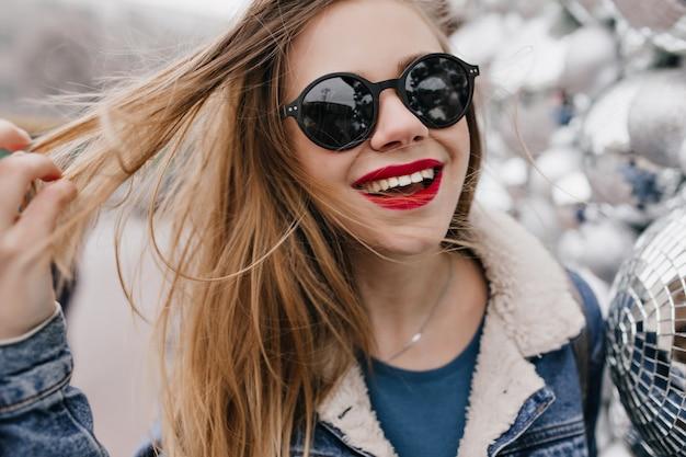 Close-up shot van innemende meisje met rode lippen spelen met haar haar en lachen op stedelijke straat. foto van vrij kaukasische vrouw die in zwarte zonnebril de lentegang geniet. Gratis Foto