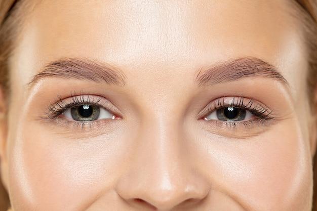 Close-up shot van jonge vrouw op gele studio Gratis Foto