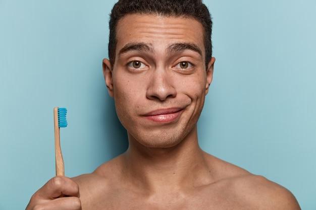 Close-up shot van jongere met een gezonde huid, sterk lichaam, tandenborstel houdt, ochtend hygiënische procedures, staat tegen blauwe muur. hygiëne, tandverzorging en schoonheidsconcept Gratis Foto