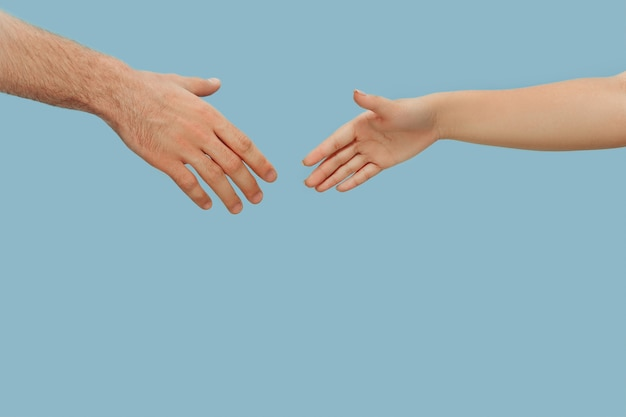 Close-up shot van menselijke hand in hand geïsoleerd. concept van menselijke relaties, vriendschap, partnerschap. copyspace. Gratis Foto
