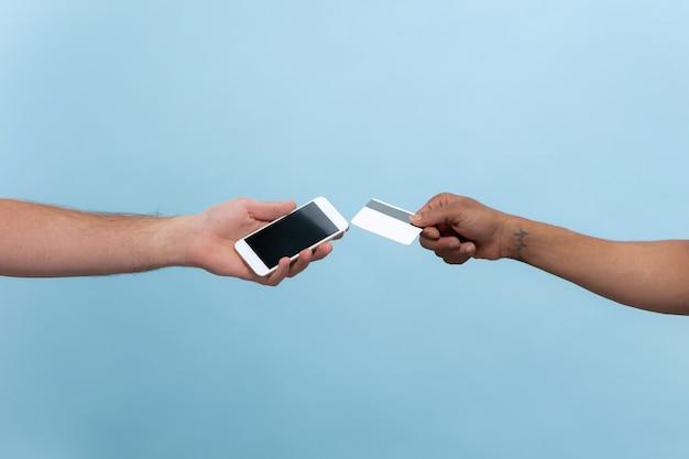 Close-up shot van menselijke hand in hand geïsoleerd op blauwe muur. relaties, vriendschap, partnerschap, bedrijf of familie. copyspace. met een kaart en een smartphone. factuur voor online betalingen. Gratis Foto