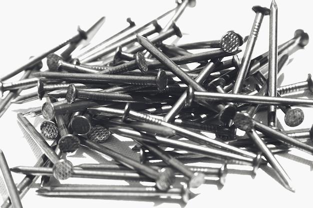 Close-up shot van metalen nagels op een wit oppervlak Gratis Foto