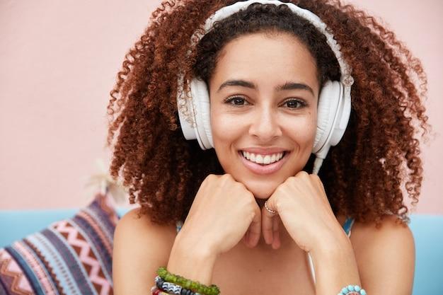 Close-up shot van mooie opgetogen jonge afrikaanse vrouw heeft een brede glimlach, geniet van favoriete melodie in koptelefoon Gratis Foto