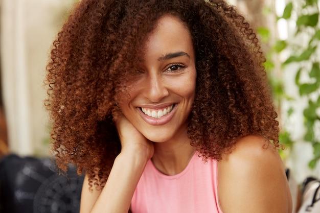 Close-up shot van positieve donkere huid tienermeisje heeft afro kapsel, terloops gekleed, heeft een stralende glimlach, berust binnen met goede vriend of vriend, in goed humeur. mensen, schoonheid, ethiniciteit Gratis Foto