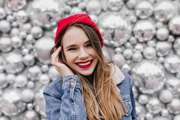 Close-up shot van prachtige blanke vrouw met lang haar glimlachend op fonkelingsmuur in koude dag. extatisch meisje in rode hoed en spijkerjasje lachen tijdens fotoshoot. Gratis Foto