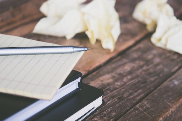 Close-up shot van schoolboeken met een grijze pen en verfrommelde stukjes papier rond op een houten oppervlak Gratis Foto