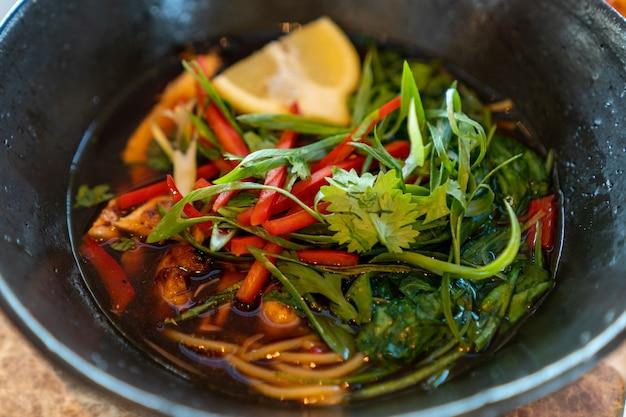 Close-up shot van soep met groenten citroen en greens in een zwarte plaat Gratis Foto