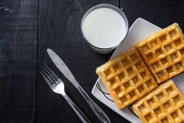 Close-up shot van vierkante wafels en melkglas op een houten tafel Gratis Foto