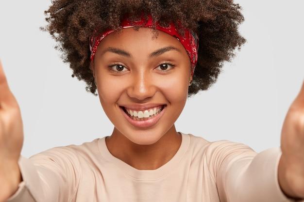 Close-up shot van vrolijke donkere meisje praat met vriendje via online video, maakt selfie met onherkenbaar apparaat, heeft een brede glimlach, modellen over witte muur, trekt handen naar voren Gratis Foto